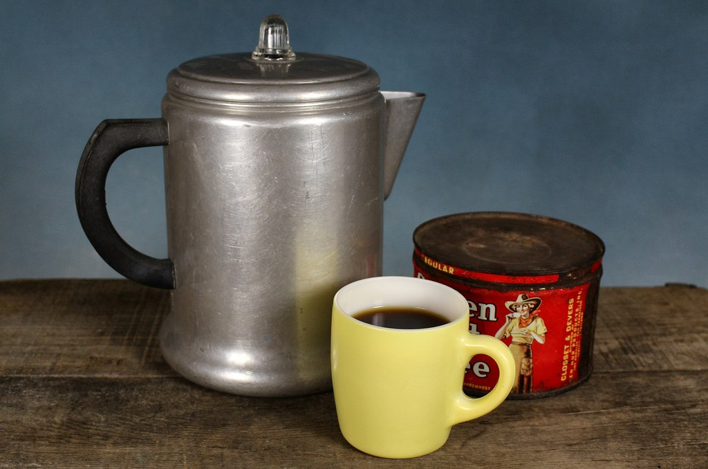 Old percolator with ground coffee and mug.